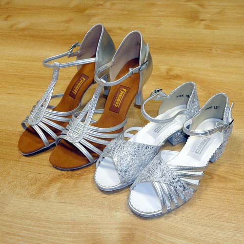 A childrens size ballroom and latin shoe compared with an adults sized shoe.